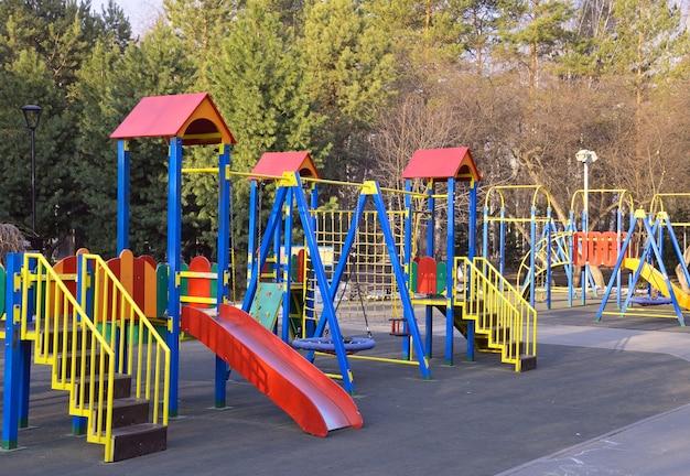 Plac zabaw dla dzieci w parku kolorowe huśtawki zjeżdżalnie drabinki poziome drążki