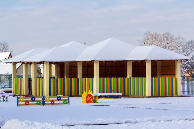 Plac zabaw w przedszkolu w zimie z huśtawkami pokrytymi śniegiem