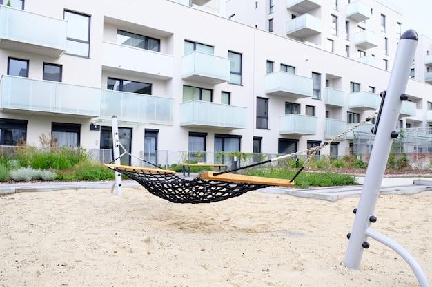 Plac zabaw z hamakiem na przytulnym dziedzińcu nowoczesnej dzielnicy mieszkalnej.