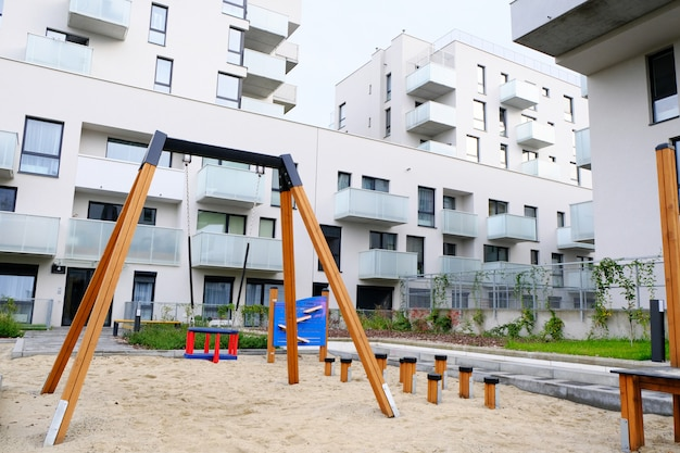 Plac zabaw z huśtawką na przytulnym dziedzińcu nowoczesnej dzielnicy mieszkalnej.