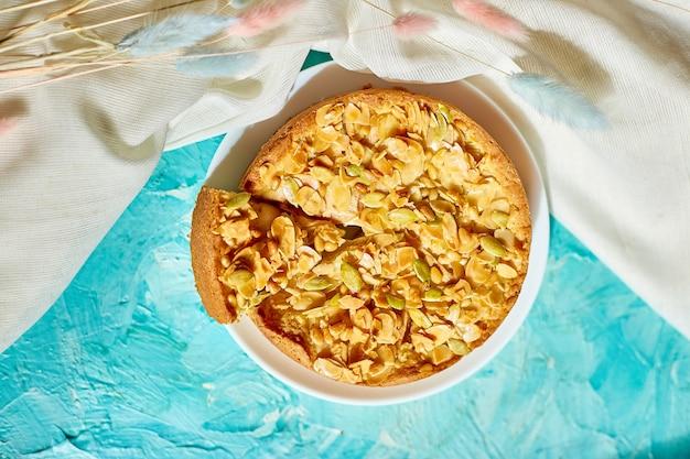 Placek jabłkowy lub gruszkowy, tarta z karmelowymi orzechami na niebieskim stole w świetle słonecznym