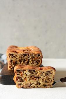 Placek naleśnikowy z mięsem i grzybami. ciasto naleśnikowe w postaci chleba. kuchnia słowiańska. placek naleśnikowy z mięsem i grzybami