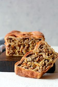 Placek naleśnikowy z mięsem i grzybami na szarym tle. ciasto naleśnikowe w formie chleba.