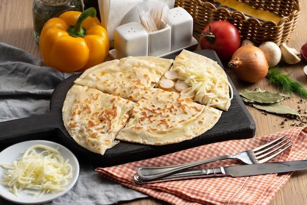 Placek z nadzieniem kiełbaskowo-serowym mozzarella na drewnianej desce do krojenia