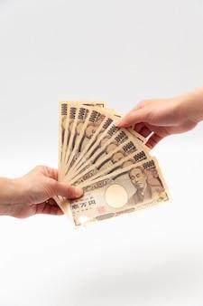 Płacenie i otrzymywanie 100 000 jenów na 10 izolowanych banknotach japońskich