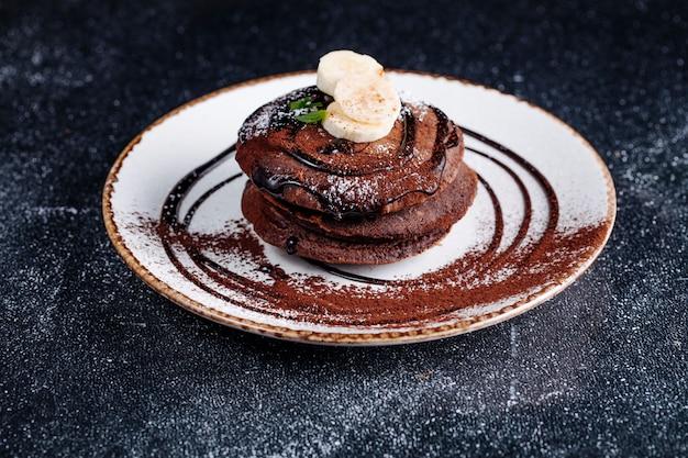 Placki czekoladowe z syropem czekoladowym i bananem.