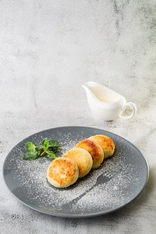 Placki twarogowe, syrniki lub serniki ze śmietaną, miodem, miętą na białym tle na białym tle z marmuru. domowe jedzenie. smaczne śniadanie. selektywne ustawianie ostrości. zdjęcie pionowe.