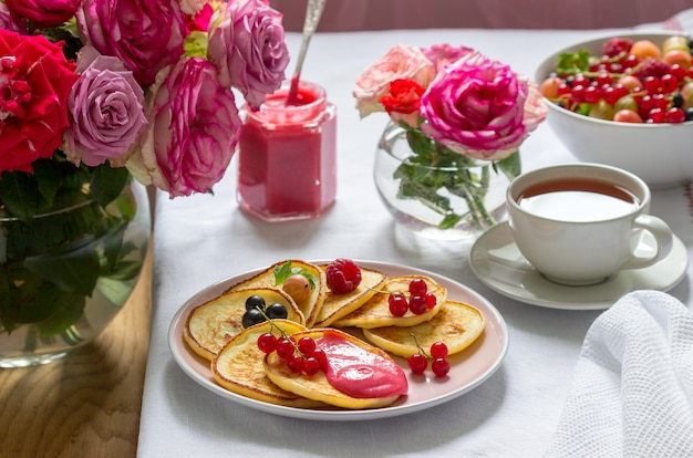 Placki twarogowe z twarogiem jagodowym podawane z herbatą na stole ozdobionym bukietami róż.