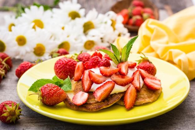 Placki z jogurtem, pokrojonymi truskawkami i liśćmi mięty na talerzu i bukiet stokrotek