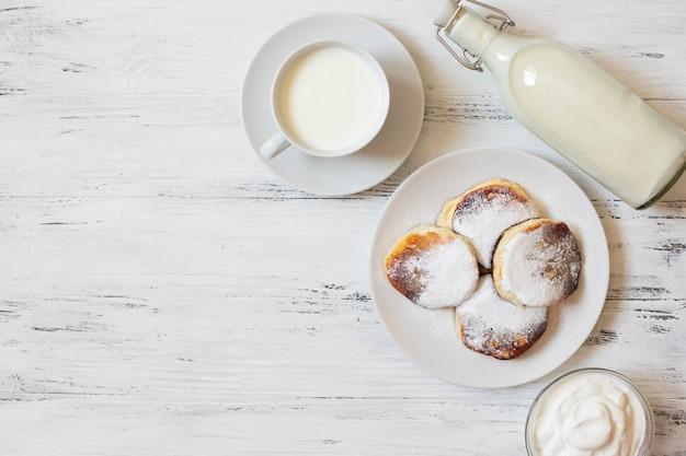Placki z twarogiem. serniki syrniki lub sirniki. zdrowe śniadanie. białe naczynia. butelka mleka. kubek mleka. jogurt lub śmietana. białe tło. widok z góry. miejsce na tekst