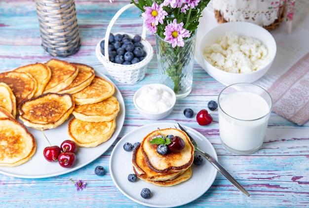 Placki z twarogiem (syrniki). domowe serniki z twarogu z kwaśną śmietaną, jagodami i mlekiem. tradycyjne danie rosyjskie. zbliżenie.