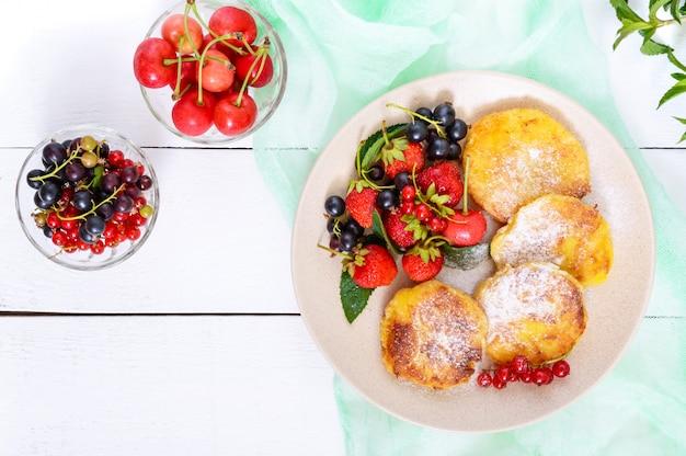 Placki z twarogu ze świeżymi jagodami na talerzu