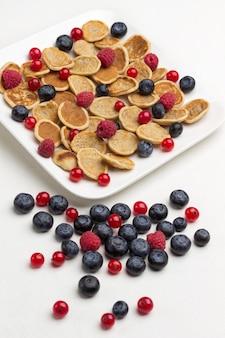 Placki zbożowe, maliny i jagody na białym talerzu ceramicznym. jagody i czerwone porzeczki na białej powierzchni. leżał na płasko.
