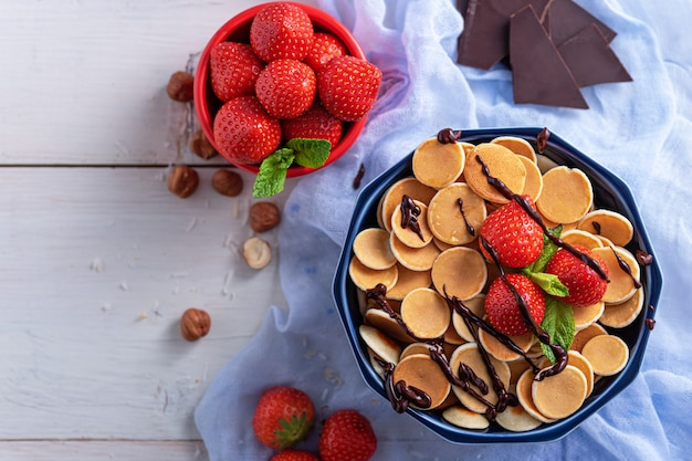 Placki zbożowe w niebieskiej misce z truskawkami, orzechami laskowymi i czekoladą na niebieskim gazie na białym drewnianym