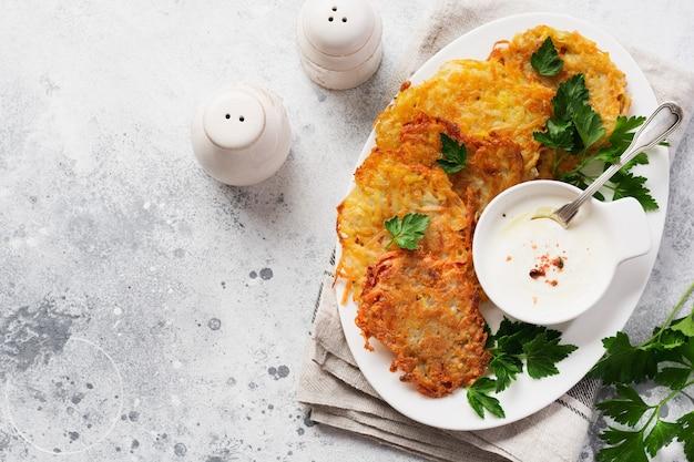Placki ziemniaczane draniki, wegetariańskie placki ziemniaczane, podawane ze świeżymi ziołami i sosem jogurtowo-czosnkowym