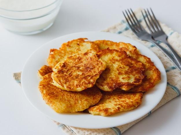Placki ziemniaczane lub tradycyjny domowy przepis na latke ze smażonymi warzywami. zdrowe organiczne jedzenie wegańskie