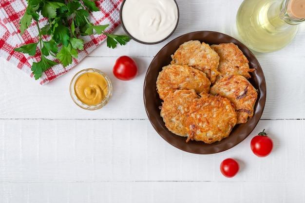 Placki ziemniaczane na talerzu na białym drewnianym stole. menu wegetariańskie. widok z góry