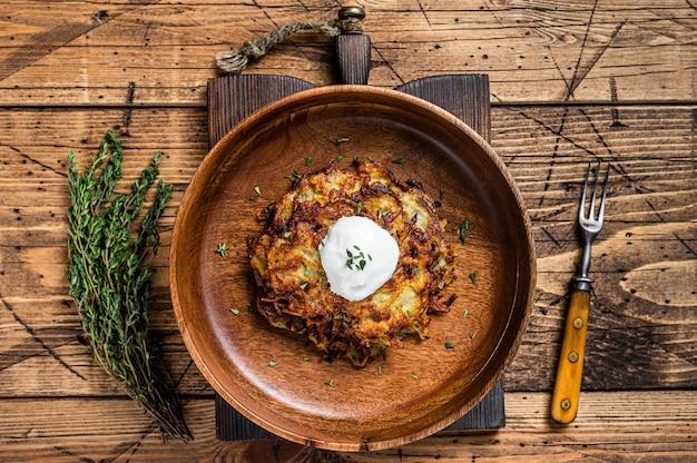 Placki ziemniaczane pieczone lub placuszki z ziołami w drewnianym talerzu. drewniane tła. widok z góry.