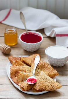 Placki żytnie i pełnoziarniste podawane z kwaśną śmietaną, miodem i sosem truskawkowym. styl rustykalny.