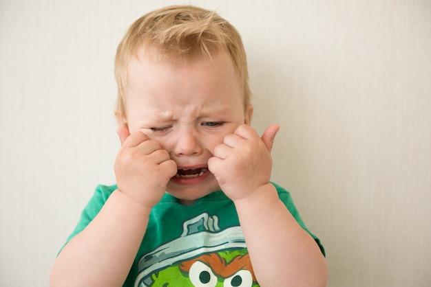 Płacz chłopca zakrywa jej twarz rękami