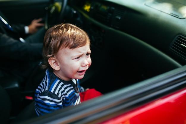 Płacz chłopiec w samochodzie.