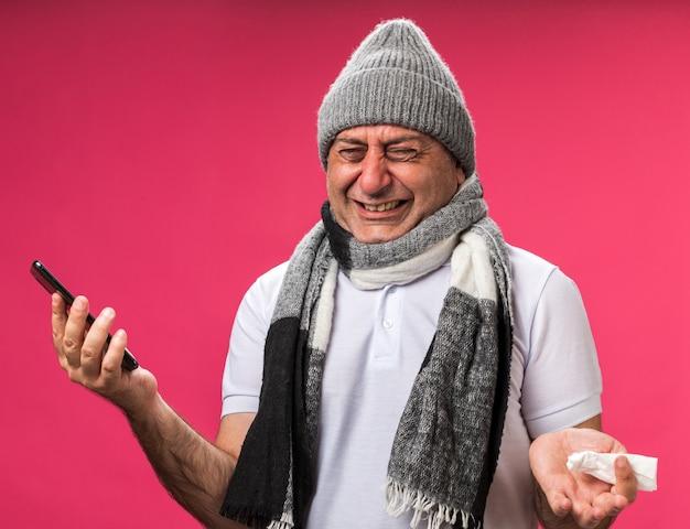 Płacz dorosły chory kaukaski mężczyzna z szalikiem na szyi w czapce zimowej trzymającej telefon i serwetkę odizolowanych na różowej ścianie z kopią przestrzeni