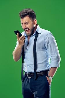 Płacz emocjonalny zły człowiek krzyczy na telefon komórkowy na zielonym studio.