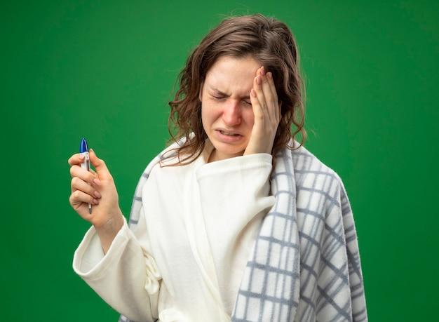 Płacz młoda chora dziewczyna ubrana w białą szatę zawiniętą w kratę trzymając termometr kładąc rękę na czole na białym tle na zielono