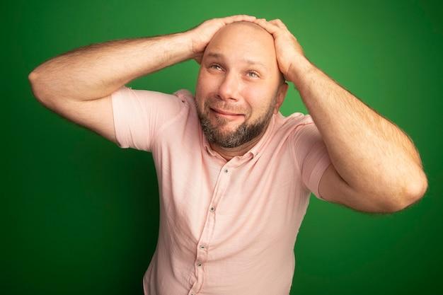 Płacząc patrząc w górę łysy mężczyzna w średnim wieku ubrany w różową koszulkę chwycił głowę