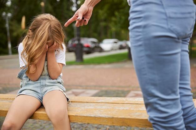 Płacząca dziewczyna trzymająca dłoń na twarzy siedząca na ławce w miejskim parku