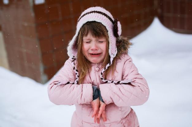 Płacząca dziewczyna w różowej kurtce delikatnie marznie na zewnątrz w zimie, śnieg, emocje