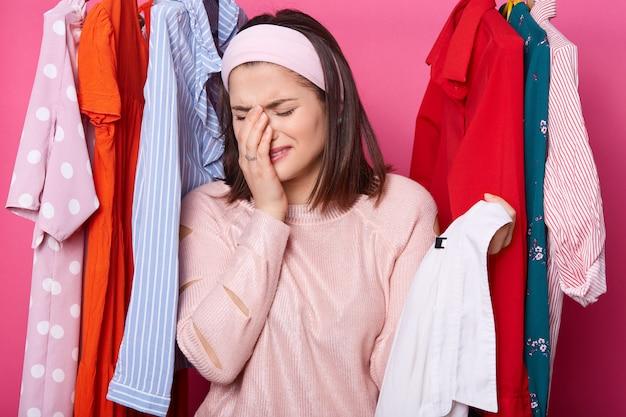 Płacząca kobieta trzymając prawą rękę w pobliżu twarzy i trzymając wieszak z białą koszulą podczas