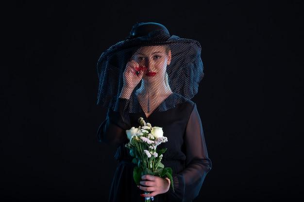 Płacząca kobieta ubrana na czarno z kwiatami na czarnej powierzchni śmierć smutek pogrzeb