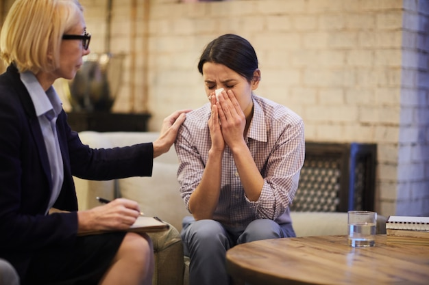 Płacząca kobieta w sesji terapeutycznej