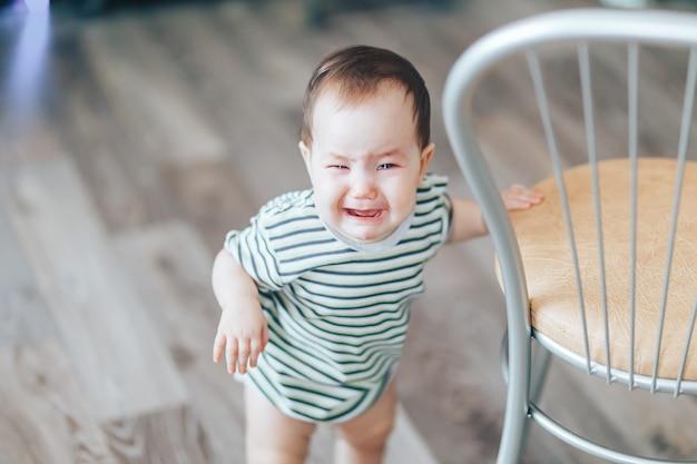 Płacząca mała ślicznotka z długimi włosami stoi głośno płacząc, stojąc w domu obok krzesła