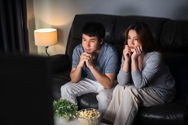 Płacząca młoda para oglądając romantyczny film telewizyjny na kanapie w nocy