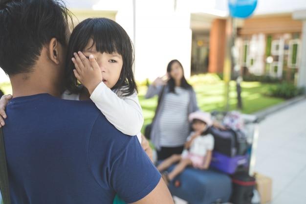 Płaczące małe dziecko było noszone przez jego ojca