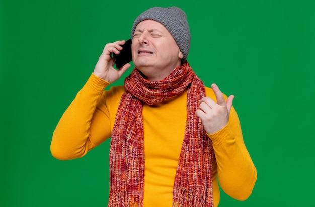 Płaczący dorosły słowiański mężczyzna w czapce zimowej i szaliku na szyi rozmawiający przez telefon