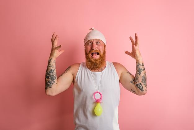 Płaczący mężczyzna z brodą i tatuażami zachowuje się jak mały noworodek