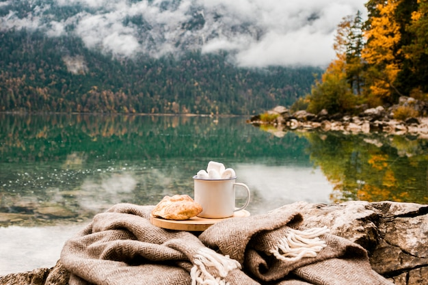 Plaid, croissant, cacao, with marshmallow near lake in bavarian alps, germany