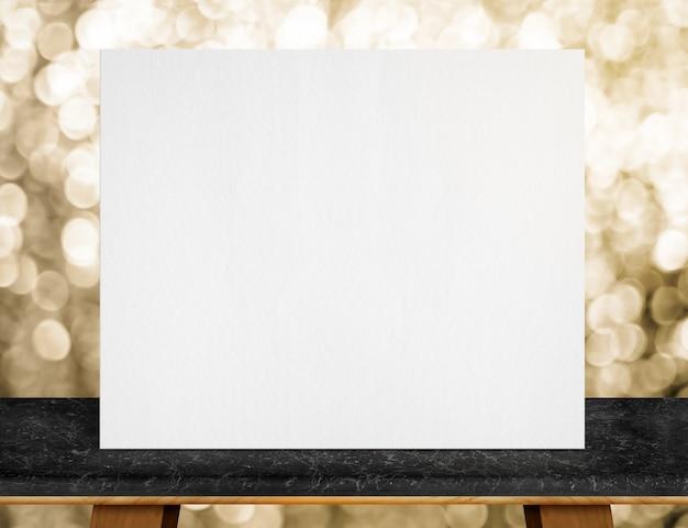 Plakat z białego papieru na czarnym marmurowym blacie i błyszczące złote światło bokeh