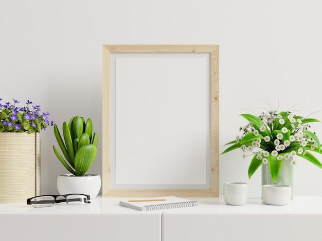 Plakat z pionową ramą na stole i białą ścianą