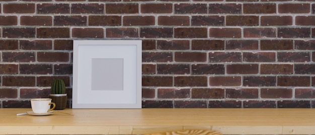 Plakat z ramą makiety do wyświetlania dzieła sztuki na drewnianym stole z pustą przestrzenią nad ścianą z czerwonej cegły