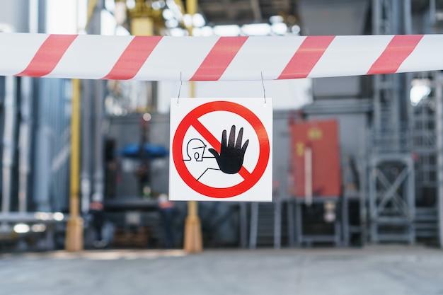 Plakat z zakazaną strefą na czerwono-białej wstążce ogrodzącej przejście na tle rur elektrowni. osoby nieupoważnione nie mają wstępu do fabryki