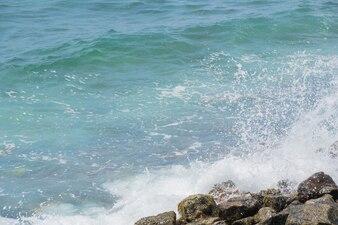 Plamy fal uderzających o kamienie przybrzeżne.