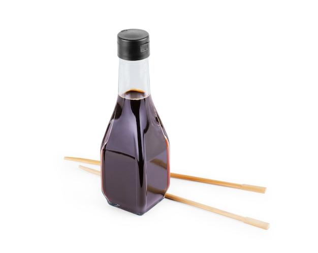 Plamy sosu sojowego i pałeczki na białym tle. maczane drewniane pałeczki