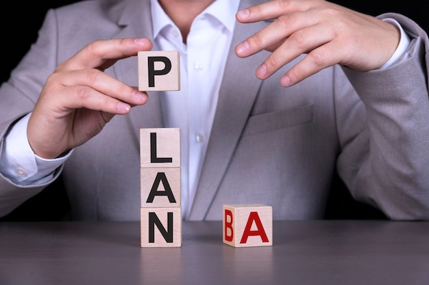 Plan a, plan b, słowo zapisane na drewnianych kostkach, na tle biznesmen w szarym garniturze.