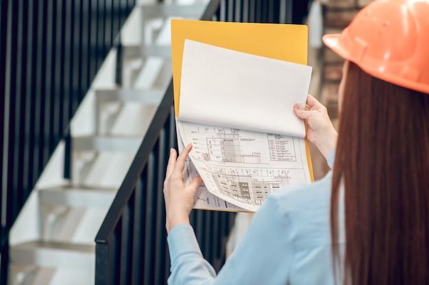 Plan budowy w rękach kobiety z plecami