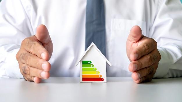 Plan domu z wykresami oszczędzania energii i czystej energii w rękach biznesowych