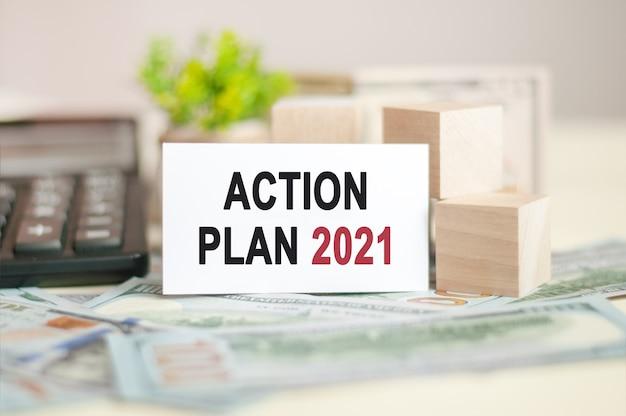 Plan działania 2021 tekst na białym papierze, na temat bonów pieniężnych, banknotów i drewnianych klocków, koncepcja biznesowa